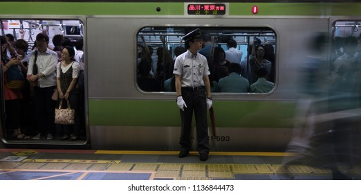 TOKYO, JAPAN - JULY 16TH, 2018. Japan Railway staff on duty during  the morning rush hour in Shibuya Station. Selective focusing.