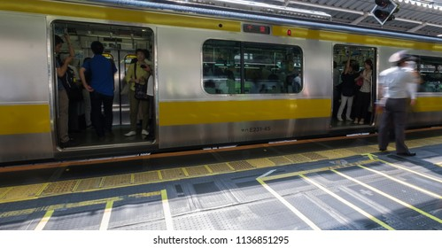 TOKYO, JAPAN - JULY 16TH, 2018. Selective focus motion blur of commuters   at Shinjuku Japan Railway station platform during the morning rush hour.