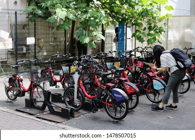 TOKYO, JAPAN - July 19, 2018:  A cyclist inputs a code into an E-bikes belonging to Toyko's public bicycle sharing scheme in Toyko's Toranomon area.  A public smoking area is in the background.