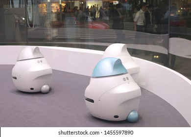 TOKYO, JAPAN - July 19, 2019: A group of Nissan EPORO robot cars in Nissan Crossing's showroom window in Ginza seen in the evening. A busy street can be seen outside.
