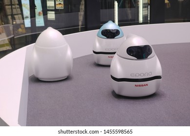 TOKYO, JAPAN - July 19, 2019: A group of Nissan EPORO robot cars in Nissan Crossing's showroom window in Ginza seen in the evening.