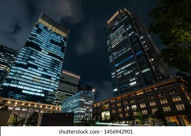 TOKYO, JAPAN - JULY 19TH, 2019. Illuminated modern building at Maranouchi district at night.