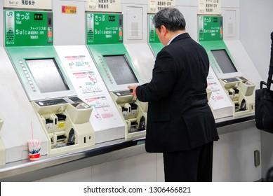 TOKYO, JAPAN - JULY 22, 2008: A Japanese gentleman in front of ticketing machines at Shinjuku main station at night.