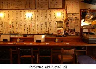 TOKYO, JAPAN - JULY 23, 2019: Very typical sushi restaurant in Tokyo with names of dishes written in japanese letters everywhere around the counter.