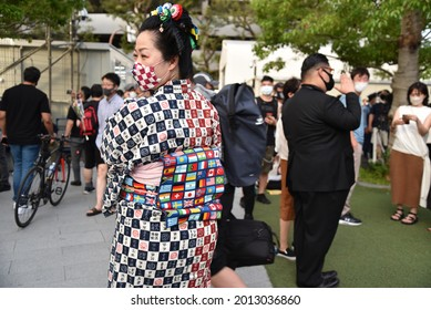 Tokyo, Japan - July 23, 2021 : A Japanese woman wearing a unique kimono with national flags of the world pattern on her obi to celebrate Tokyo Olympics 2020