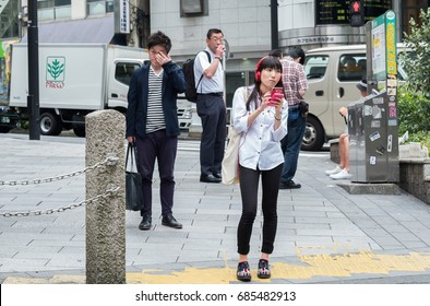 TOKYO, JAPAN - JULY 27TH, 2017. Girl with smartphone waiting to cross the street in Shibuya.