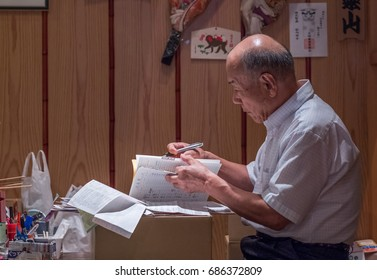 TOKYO, JAPAN - JULY 29TH, 2017. Elderly man concentrating on his work in a shop in Kagurazaka street.