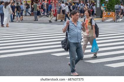 TOKYO, JAPAN - JULY 30TH, 2017. Man crossing the street in Kabukicho, Shinjuku.