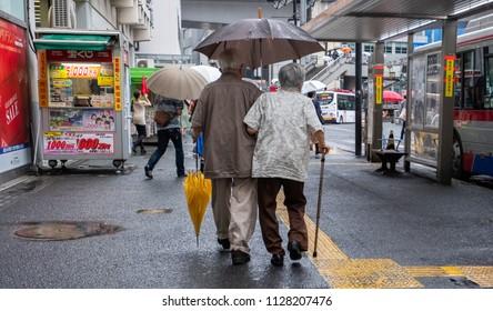 TOKYO, JAPAN - JULY 4TH, 2018. Old Japanese couple walking at a bus stop with umbrella during a rainy day, Shibuya