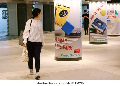 TOKYO, JAPAN - July 5, 2019: A subterranean concourse with pillars with adverts for '#009 Walkman in the Park', an exhibition held to commemorate the Walkman's 40th anniversary. Some motion blur.