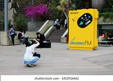 TOKYO, JAPAN - July 5, 2019: A visitor takes a photo of a giant model of a Sony Sports Walkman at Ginza Sony Park. It is part of the '#009 Walkman in the Park'.