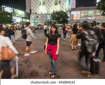 Tokyo, Japan - Jun 6, 2016 : A Girl standing at Shibuya the world busiest crossing road. People are waiting to cross the junction, the travelers also keep walking such a crowded area of Toyko, Japan.