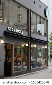 TOKYO, JAPAN - June 1, 2018: View of a branch of Starbucks branch in Tokyo's Ginza area at dusk. This branch was the first Starbucks to open in Japan.