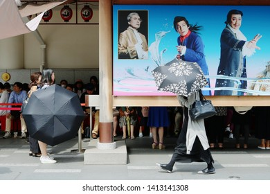 TOKYO, JAPAN - June 1, 2019: Section of the front of Ginza 's Kabuki-za kabuki theater on a hot day with people waiting in the shade behind a billboard.
