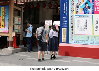TOKYO, JAPAN - June 1, 2019: People look at leaflets & posters front of Ginza 's Kabuki-za kabuki theater. In the background people wait in the shade to enter the theater.