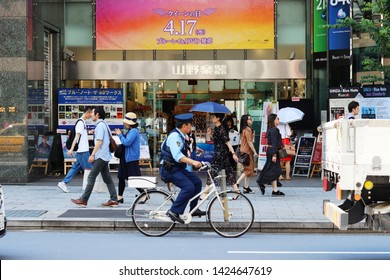 TOKYO, JAPAN - June 13, 2019: View of street in front of Ginza's Yamano Music Store with people using parasols & cycle riding police officer on patrol. The billboard is for the film Bohemian Rhapsody.