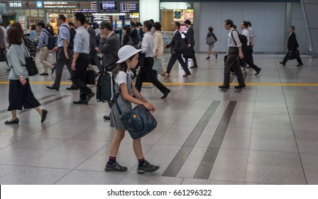 TOKYO, JAPAN - JUNE 15TH 2017. Selective focus on a school girl during rush hour at Shinagawa station. The weekday rush hours peak and most extreme between 8am and 9am in the morning.