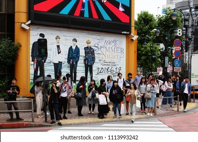 TOKYO, JAPAN - June 16, 2018:  People at a crossing in front of the edge of the large Shibuya branch of Tower Records. Behind them is a large poster advertising a single by K-Pop band 100%.