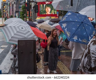 TOKYO, JAPAN - JUNE 18TH 2017. Crowd of people at the famous Shibuya crossing during a rainy night. The rainy season, locally known as tsuyu or baiyu, begins the from June until mid July in Japan.