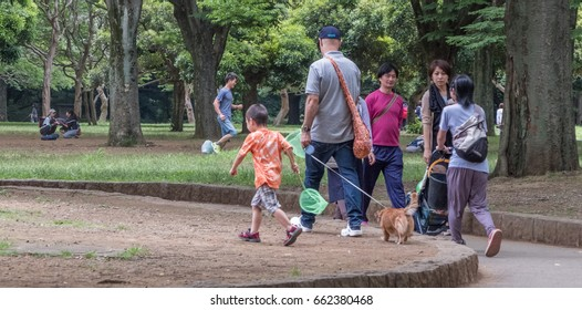 TOKYO, JAPAN - JUNE 18TH 2017. Family walking in Yoyogi Park. The park is a very popular public in Tokyo and is a favorite destination for recreational activities in Tokyo.