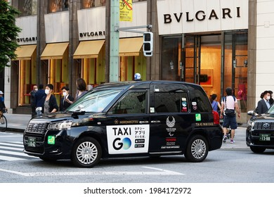 TOKYO, JAPAN - June 2, 2021: Street in Ginza in front of a Bulgari store with taxi and pedestrians.  The car is Toyota JPN taxi with a Tokyo Paralympic logo on it. Some motion blur.