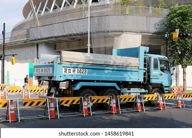 TOKYO, JAPAN - June 21, 2019: A truck on the site of road works with the National Stadium being built for the 2020 Olympics behind it.