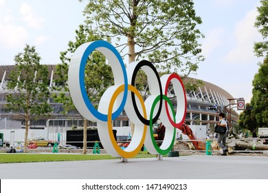 TOKYO, JAPAN - June 21, 2019: Olympic Rings monument at Tokyo Sport Olympic Square, the headquarters of JSPO & JOC. Opposite is  the under-construction National Stadium being built for 2020 Olympics.
