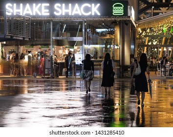 TOKYO, JAPAN  - JUNE 21ST, 2019. People walking at an eatery after a rainy night in Ginza street.