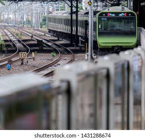 TOKYO, JAPAN  - JUNE 21ST, 2019. Japan Railway Yamanote train arriving at Harajuku Station platform. Selective focus.