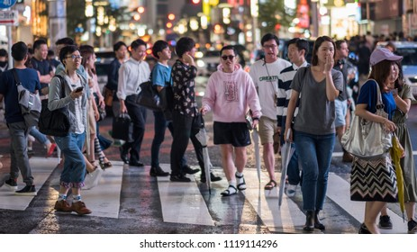 TOKYO, JAPAN - JUNE 23RD, 2018. People walking in the street of Shibuya at night.
