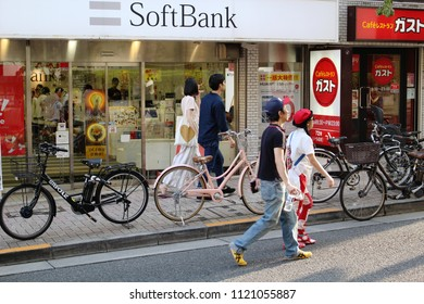 TOKYO, JAPAN - June 24, 2018: View of a street in the hilly Kagurazaka area with a Softbank branch and a Gusto restaurant. People can walk in the road because it's regularly pedestrianized.
