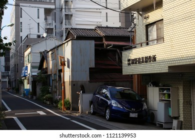 TOKYO, JAPAN - June 24, 2018: A pedestrian checks her phone on a street with a mixture of new and old buildings in the maze-like Kagurazaka area of Tokyo.