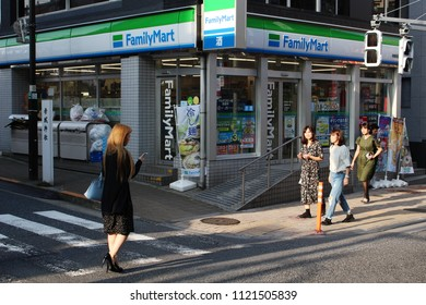 TOKYO, JAPAN - June 24, 2018: View of the sidewalk in front of a FamilyMart convenience store on the corner of a street in the hilly Kagurazaka area of Tokyo.