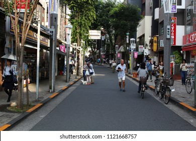 TOKYO, JAPAN - June 24, 2018: View from the bottom of sloping street in Tokyo's hilly Kagurazaka area. People are able to walk and gather in the road because it's regularly pedestrianized.