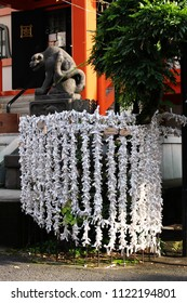 TOKYO, JAPAN - June 24, 2018: Folded O-mikuji fortune papers at Bishamonten Zenkokuji Temple in Kagurazaka. In the background there is a distinctive statue of a tiger.