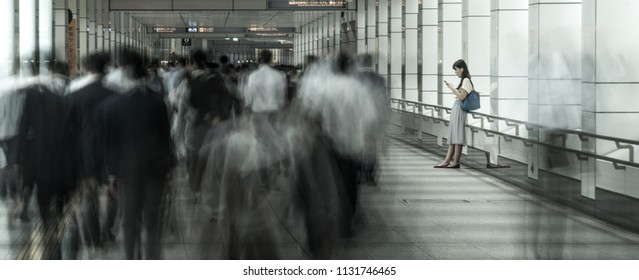 TOKYO / JAPAN - JUNE 24, 2018 /A lonely girl looks at the smartphone screen. A crowd of people passes by her. A long underground passage.