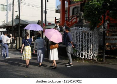 TOKYO, JAPAN - June 24, 2018: People visiting Bishamonten Zenkokuji Temple in Kagurazaka. In the background there are folded O-mikuji fortune papers & tiger statues.