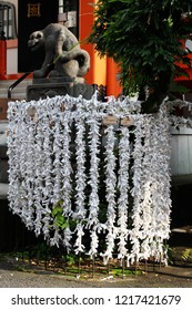 TOKYO, JAPAN - June 24, 2018: Folded O-mikuji fortune papers at Bishamonten Zenkokuji Temple in Kagurazaka. In the background is a statue of a tiger, a variation on the more common lion-dog ones.