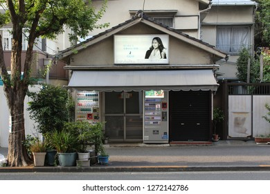 TOKYO, JAPAN - June 24, 2018: A tobacconist store in Kagurazaka with cigarette vending machines outside and an advert for IQOS smokeless cigarette devices on its roof.