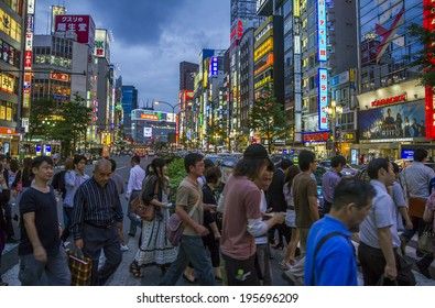 Tokyo, Japan - June 26, 2010: Crowds of people at a busy crossing in Shinjuku district in the evening with neon lights in background on 26 June 2010 in Tokyo, Japan.