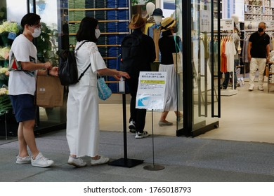 TOKYO, JAPAN - June 26, 2020: Customers use hand sanitizer before entering Uniqlo Tokyo in Marronnier Gate Ginza, after the lifting of the coronavirus state of emergency. Some motion blur.