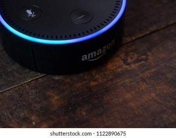 TOKYO, JAPAN - JUNE 28TH, 2018. Amazon's Echo Dot, Alexa virtual assistant on wooden board.