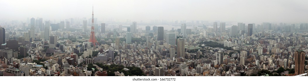 Tokyo, Japan - June 29, 2010: Wide panorama of Tokyo on a misty afternoon taken from Mori tower with industrial landscape, Tokyo Tower and Tokyo Bay in background on June 29, 2010.