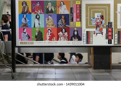 TOKYO, JAPAN - June 29, 2019: A poster inside Shimbashi subway station advertising Kabuki performances at the Kabuki-za with people climbing stairs in the background. Some motion blur.