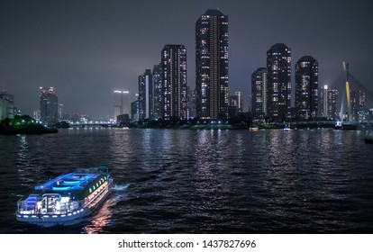 TOKYO, JAPAN - JUNE 29TH, 2019. High rise buildings in Tsukuda, Tokyo with dinner cruise houseboat (locally known as yakabutane) cruising in Sumida river in the foreground at dusk. Selective focus.