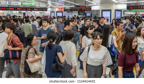 TOKYO, JAPAN - JUNE 30TH, 2018. Commuters walking between platforms at Japan Railway Shinjuku Station.