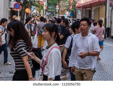 TOKYO, JAPAN - JUNE 30TH, 2018. Crowd of people walking in at the pedestrian street in Shinjuku.