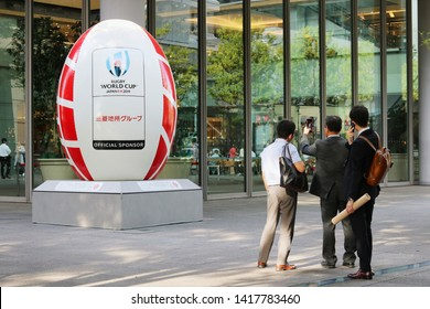 TOKYO, JAPAN - June 5, 2019: People in front of a rugby ball-shaped object promoting 2019 Rugby World Cup by a Mitsubishi Estate Co. building in Marunouchi area. The company is a tournament sponsor