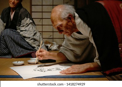 TOKYO, JAPAN - June 5, 2019: Close-up of an animatronic exhibit featuring animatronic figure of the painter Hokusai with his artist daughter Oei in the background at the Sumida Hokusai Museum.