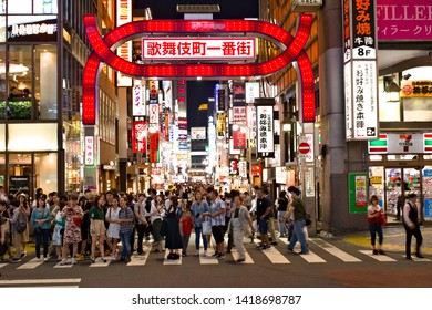 TOKYO, JAPAN - June 5, 2019: People wait to cross a street at night in front of a gate at the entrance to Shinjuku's Kabukicho area. Some motion blur.